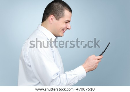 Businessman using cell phone on gray background