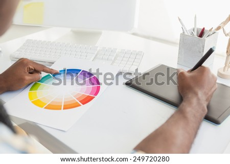 Businessman using colour sample and digitizer in the office - stock photo