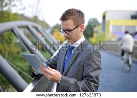 Businessman using computer tablet, Shot in the city, late afternoon/early evening. Man is wearing a gray suit and blue tie. - stock photo
