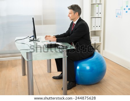 Businessman Using Computer While Sitting On Pilates Ball In Office - stock photo