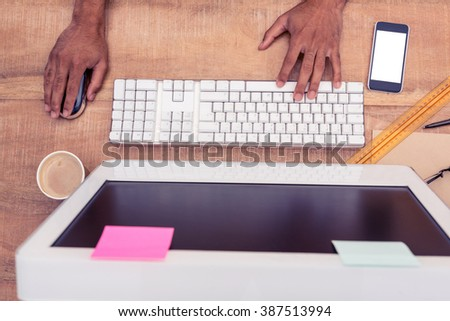 Businessman using computer while working at desk in office - stock photo