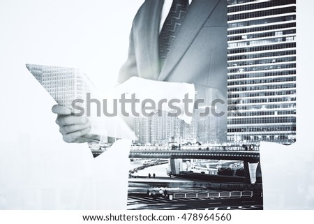 Businessman using digital pad on city background. Double exposure