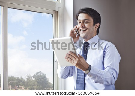 Businessman using digital tablet and talking on a cell phone - stock photo