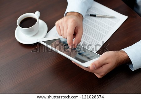 Businessman using digital tablet by the desk - stock photo