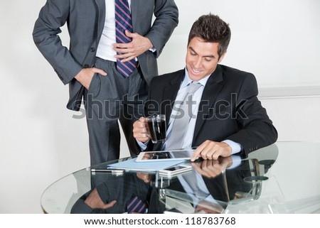 Businessman using digital tablet in a meeting with colleague at office - stock photo