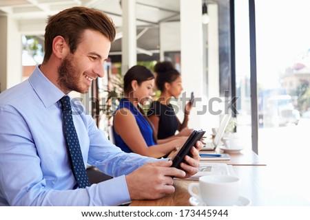 Businessman Using Digital Tablet In Coffee Shop - stock photo