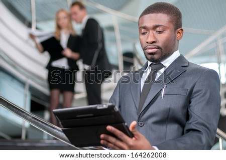 Businessman Using Digital Tablet In Office on the background of colleagues - stock photo