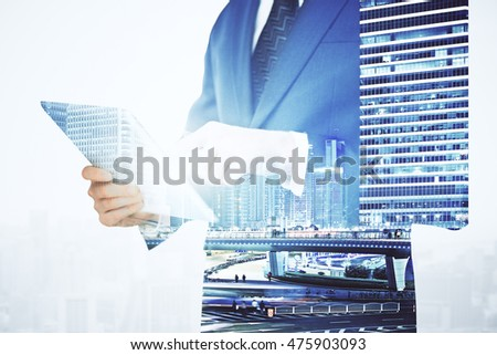 Businessman using digital tablet on city background. Double exposure