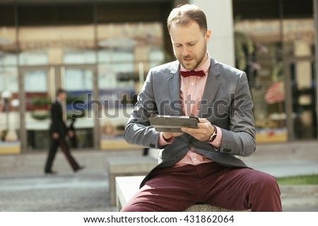 Businessman using digital tablet sitting at city avenue