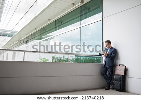 Businessman using digital tablet while waiting for the departure at the airport - stock photo