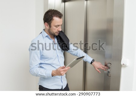 Businessman using digital tablet while waiting for the elevator