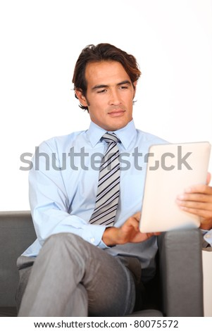 Businessman using electronic tablet in waiting room - stock photo