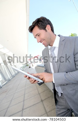 Businessman using electronic tablet outside a building - stock photo