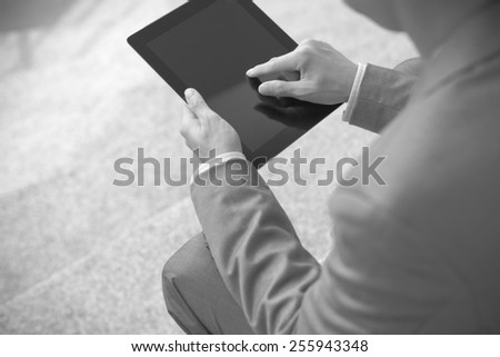 Businessman using electronic tablet pc. He is sitting on a stairs. - stock photo