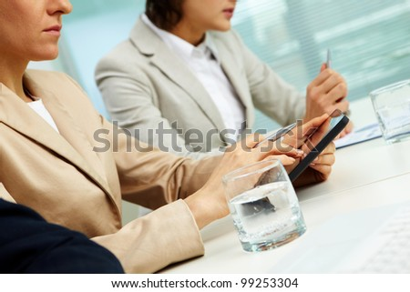 Businessman using her tablet pc, her colleagues sitting on both side of her, tilt up - stock photo