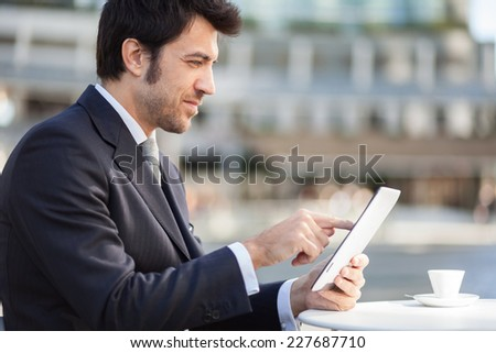Businessman using his digital tablet during breakfast - stock photo