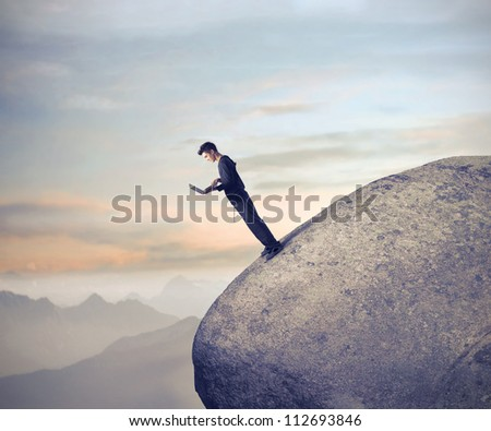 Businessman using his laptop computer on a raked rock