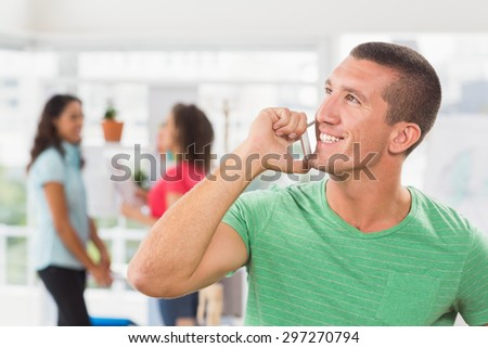 Businessman using his phone with two colleague behind him at the office - stock photo