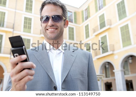 Businessman using his smart phone while standing in front of a classic office building in the city. - stock photo