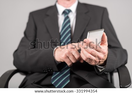 Businessman using his smartphone on grey background