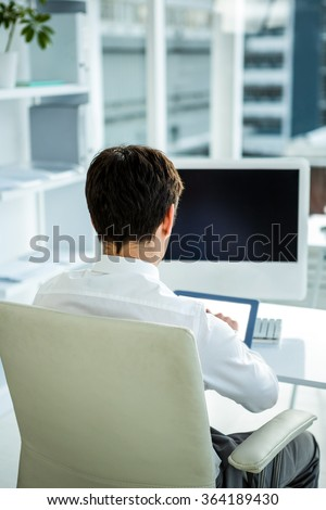 Businessman using his tablet in his office - stock photo
