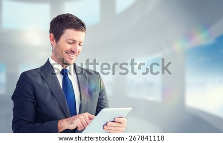 Businessman using his tablet pc against bright white room with windows - stock photo