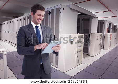 Businessman using his tablet pc against data center - stock photo