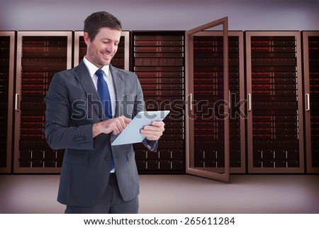 Businessman using his tablet pc against server towers - stock photo