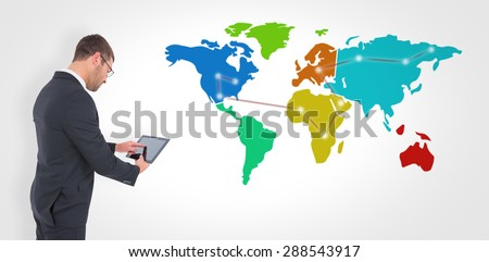 Businessman using his tablet pc against world map