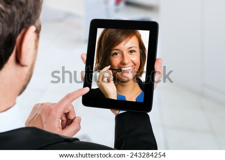 Businessman using his tablet to contact a customer representative
