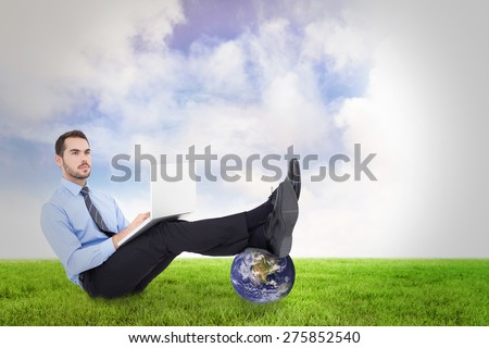 Businessman using laptop against green field - stock photo
