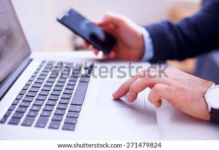 Businessman using laptop and mobile phone - stock photo