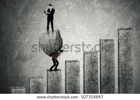 Businessman using laptop computer and standing on a big stone while his partner carrying the stone and climbing a chart