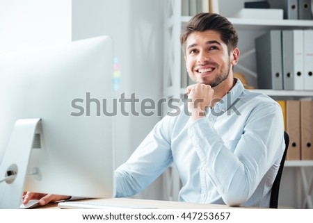 Businessman using laptop computer in office and looking at camera