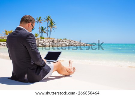 Businessman using laptop computer on tropical beach - stock photo