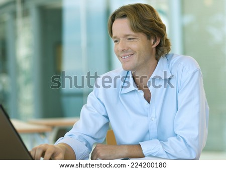Businessman using laptop computer, smiling - stock photo