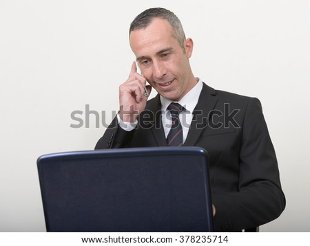 Businessman using laptop computer while talking on phone