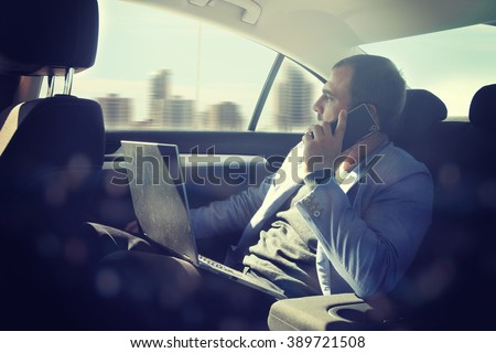 Businessman using laptop in his car - stock photo