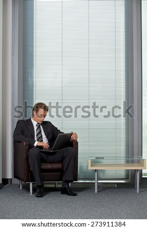 Businessman using laptop in office - stock photo