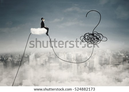 Businessman using laptop on the cloud while wearing a gas mask and looking at question mark on the sky