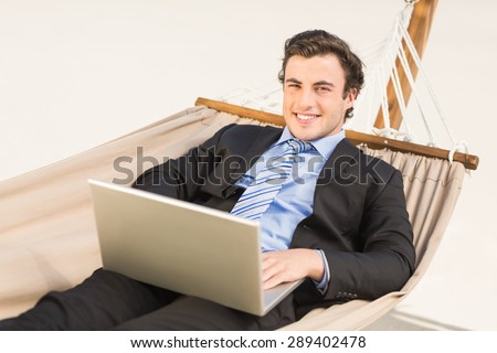 Businessman using laptop on the hammock at the beach