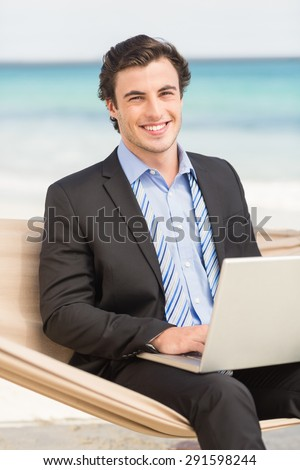 Businessman using laptop on the hammock at the beach - stock photo