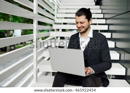 Businessman using laptop on the stairs. Male in classic outfit smiling while browsing internet.
