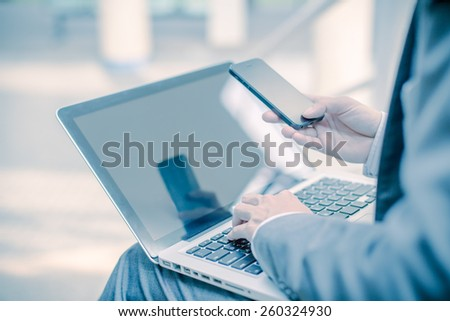 Businessman using laptop pc and mobile phone. He is sitting on a stairs. - stock photo