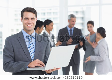 Businessman using laptop with colleagues behind in the office - stock photo