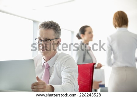 Businessman using laptop with colleagues discussing in background at office - stock photo
