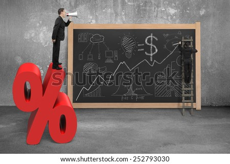 Businessman using megaphone standing on red percentage sign with business concept doodles and concrete room blackboard - stock photo
