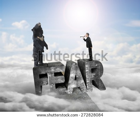 Businessman using megaphone yelling black bear at 3D mottled concrete fear word, balancing on ridge with sky sunlight cloudscape background - stock photo