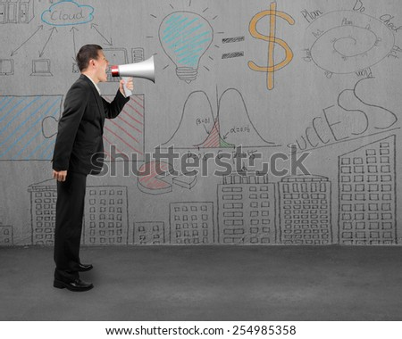 Businessman using megaphone yelling with business concept doodles wall background - stock photo