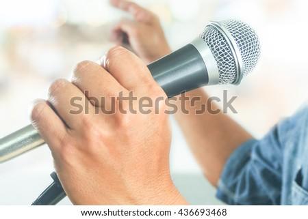 businessman using microphone for public speaking seminar presentation on bokeh background - stock photo